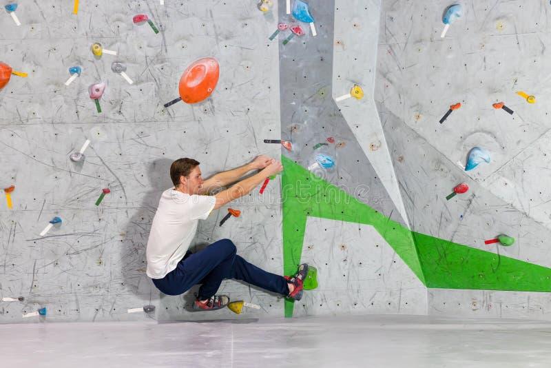 Homem do montanhista de rocha que pendura em uma parede de escalada bouldering, para dentro nos ganchos coloridos fotografia de stock royalty free