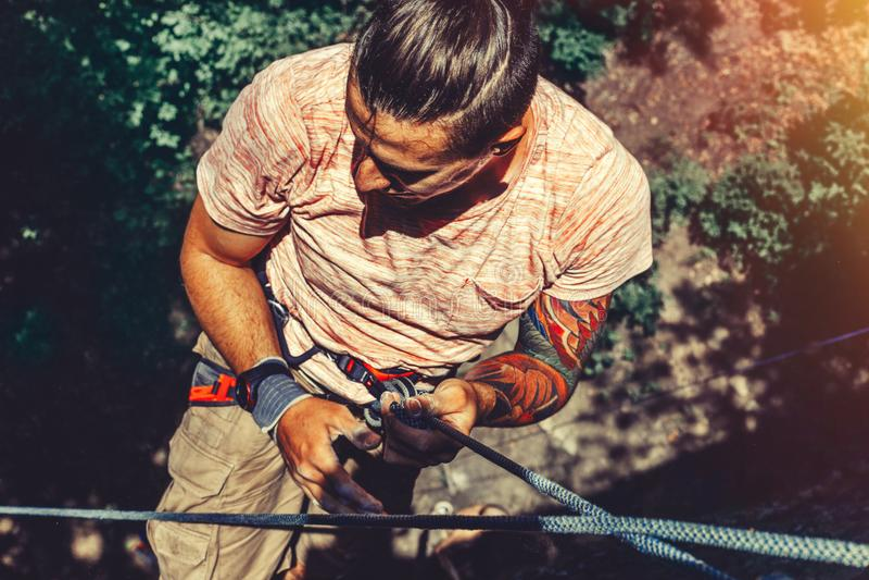 Homem do montanhista que pendura em uma rocha em uma corda e em olhares em algum lugar na parede Conceito extremo da atividade ex imagem de stock