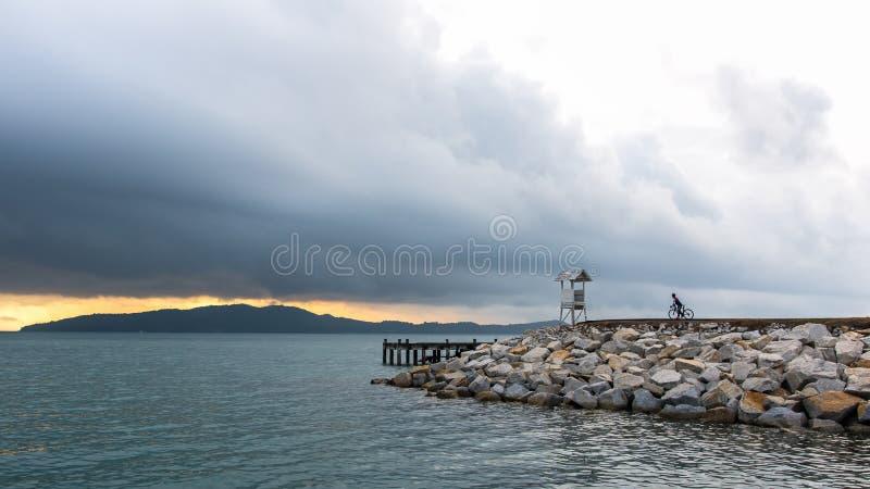Homem do motociclista com a bicicleta no farol perto do mar no nascer do sol fotos de stock