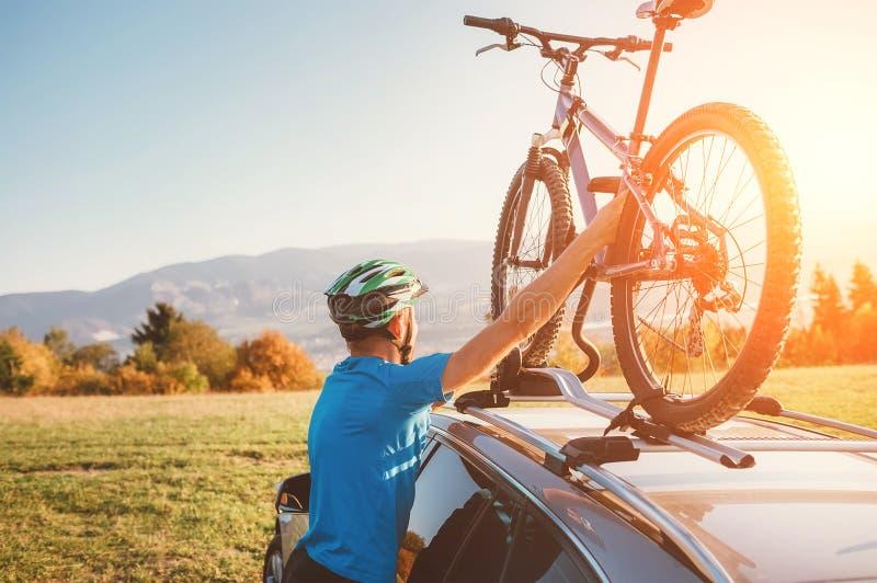 Homem do motociclista da montanha para tomar de sua bicicleta do telhado do carro imagens de stock