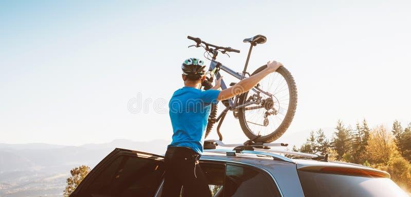 Homem do motociclista da montanha para tomar de sua bicicleta do telhado do carro fotografia de stock
