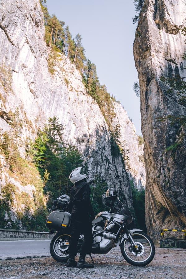 Homem do motociclista no velomotor da aventura na estrada da montanha na garganta de Bicaz, Romênia Conceito do turismo e das fér foto de stock royalty free