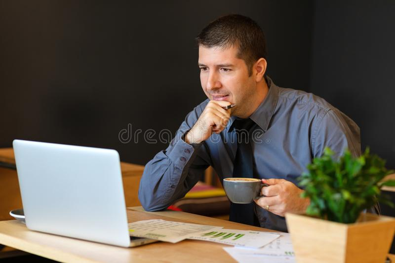 Homem do Oriente Médio maduro com funcionamento da xícara de café da terra arrendada no portátil no café moderno que analisa impo fotos de stock royalty free