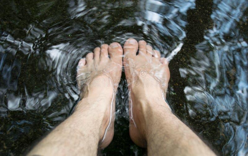 Homem do pé em termas da natureza da mola de água imagens de stock royalty free