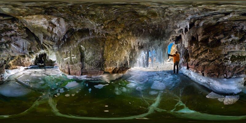 Homem do panorama em uma caverna de gelo com sincelos em Baikal, Olkhon, panorama esférico do grau de 360 vr imagem de stock