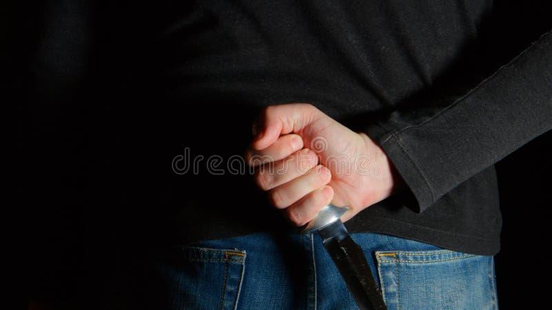 Homem do perigo com uma faca atrás da parte traseira foto de stock royalty free