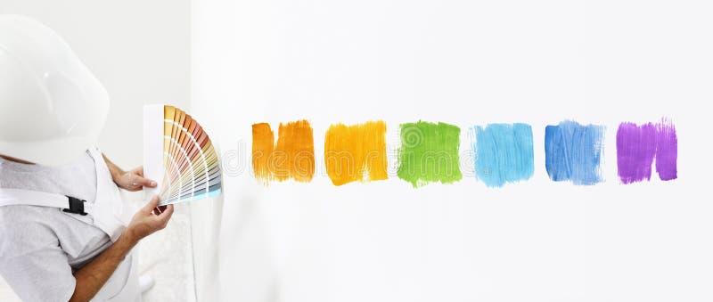 Homem do pintor com amostras de folha em sua mão, cores bem escolhidas da cor fotos de stock royalty free