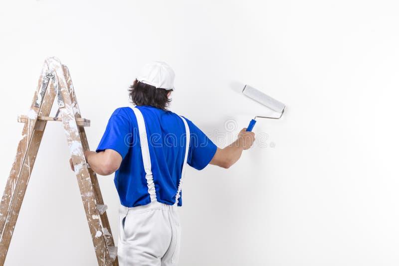 Homem do pintor no trabalho que escala uma escada e um paintin de madeira do vintage fotografia de stock royalty free