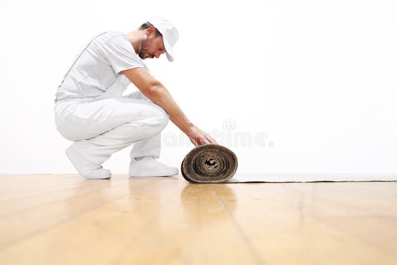 Homem do pintor no trabalho, rolos o cartão no assoalho fotografia de stock
