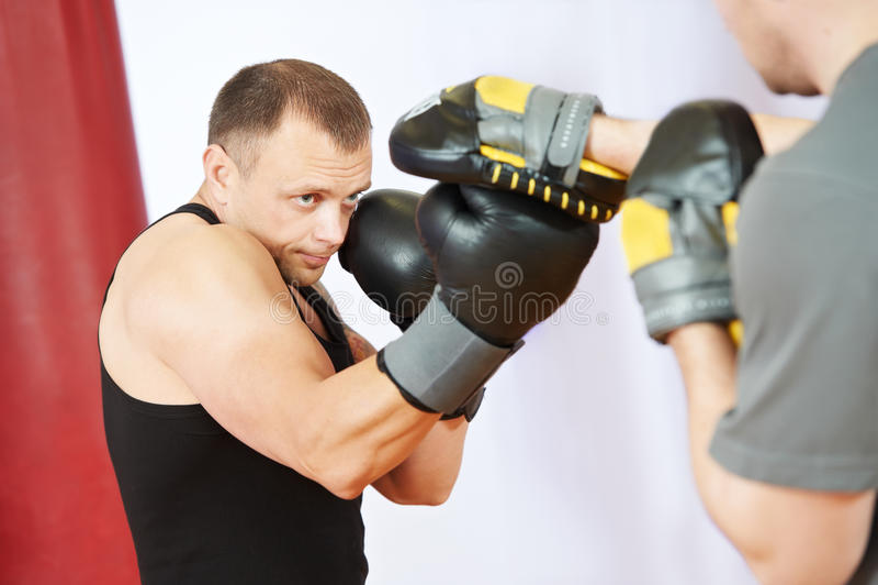 Homem do pugilista no treinamento do encaixotamento com luvas do perfurador fotografia de stock