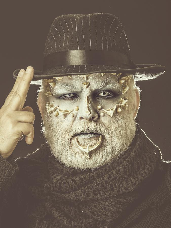 Homem do Reptilian com o chap?u negro tocante da sauda??o de dois dedos fotos de stock royalty free