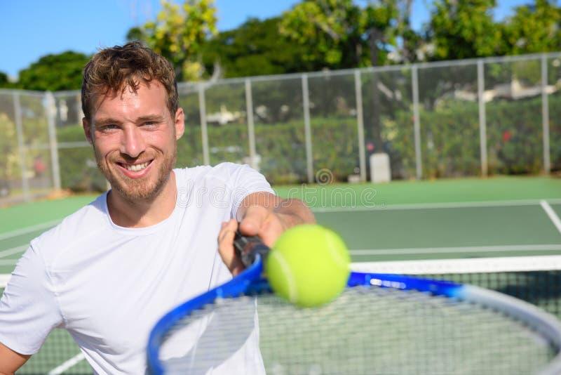Homem do retrato do jogador de tênis que mostra a bola e a raquete foto de stock royalty free