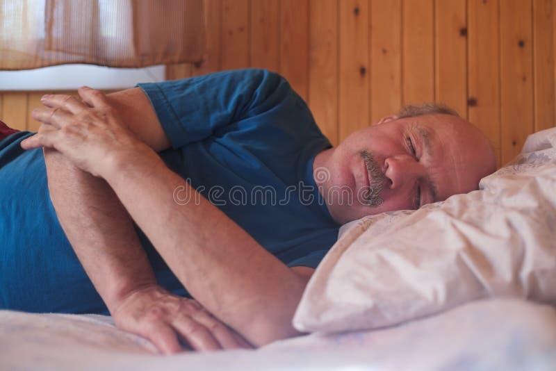 Homem do Senor que dorme na cama em casa Fim acima fotos de stock royalty free