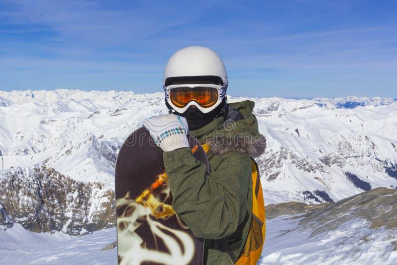 Homem do Snowboarder com vidros alaranjados do esqui no capacete branco que levanta na parte superior em montanhas dos cumes No f fotos de stock