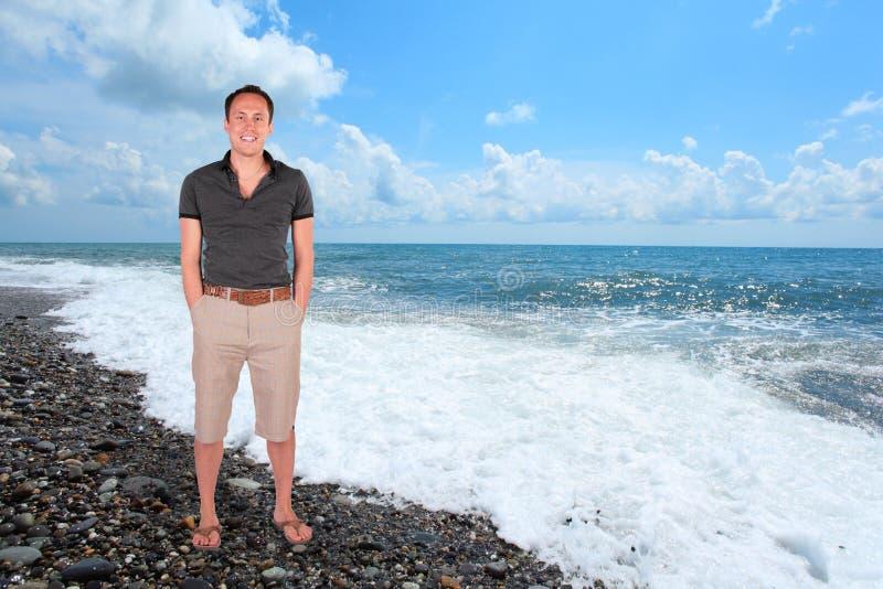 Homem do sorriso na colagem da costa do seixo imagem de stock