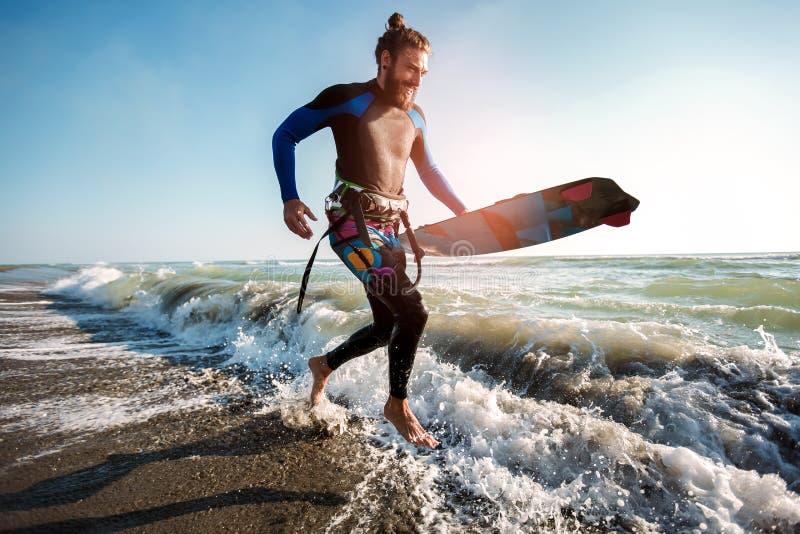 Homem do surfista com placa de ressaca na praia Atividade do esporte do ver?o fotografia de stock