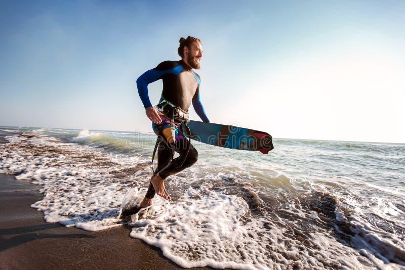Homem do surfista com placa de ressaca na praia Atividade do esporte do ver?o fotos de stock royalty free