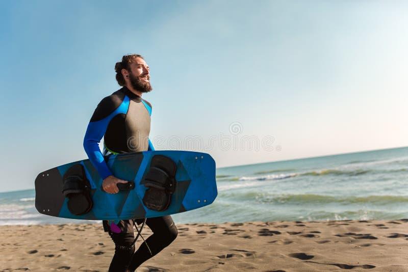 Homem do surfista com placa de ressaca na praia Atividade do esporte do ver?o fotografia de stock royalty free