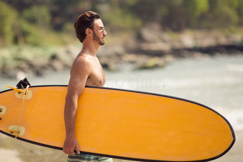 Homem do surfista com a prancha na costa de mar fotografia de stock royalty free