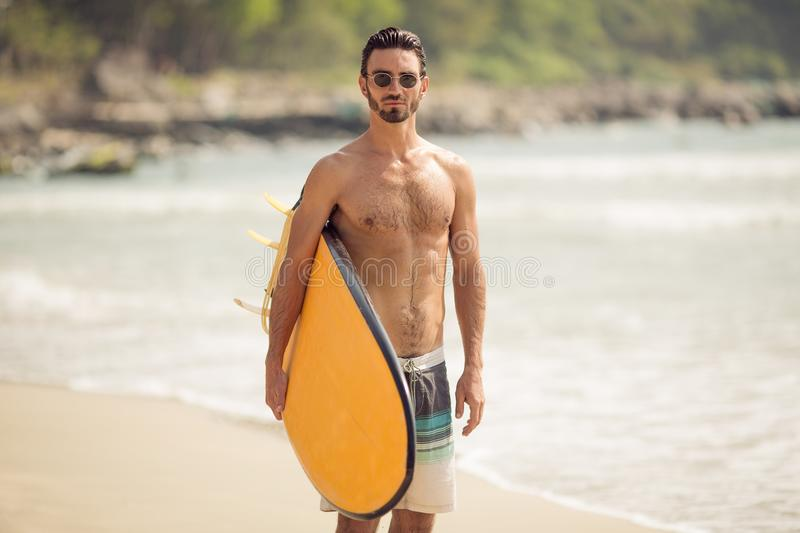 Homem do surfista com a prancha na costa de mar fotos de stock royalty free
