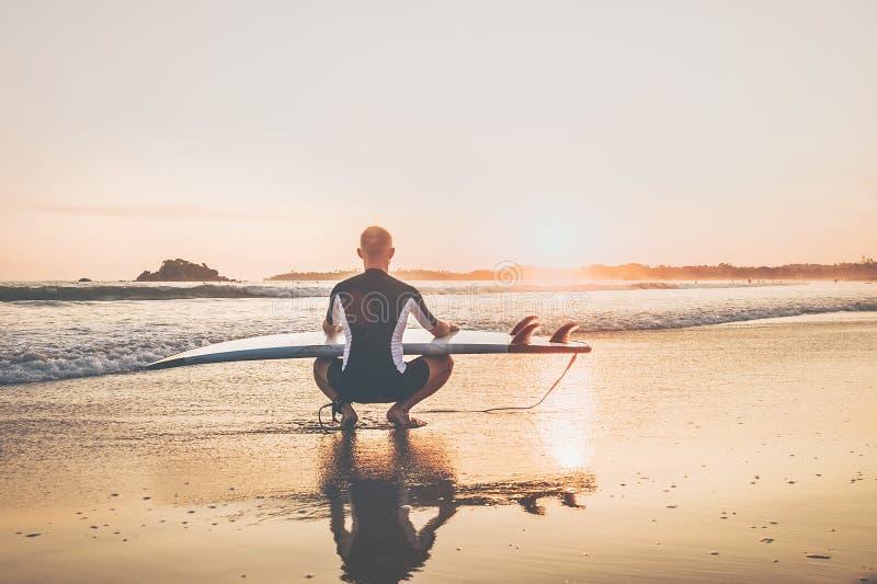 Homem do surfista com a ressaca longa da placa que senta-se na praia arenosa do oceano e que aprecia o céu do por do sol Nunca te fotografia de stock royalty free