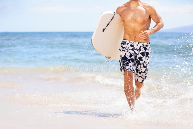 Homem do surfista do divertimento da praia que funciona com bodyboard imagem de stock royalty free
