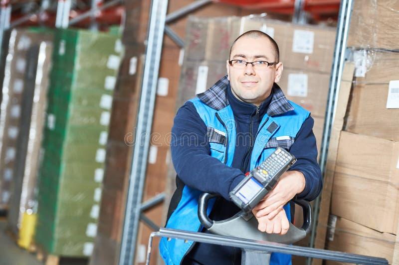 Homem do trabalhador com o varredor do código de barras do armazém fotografia de stock