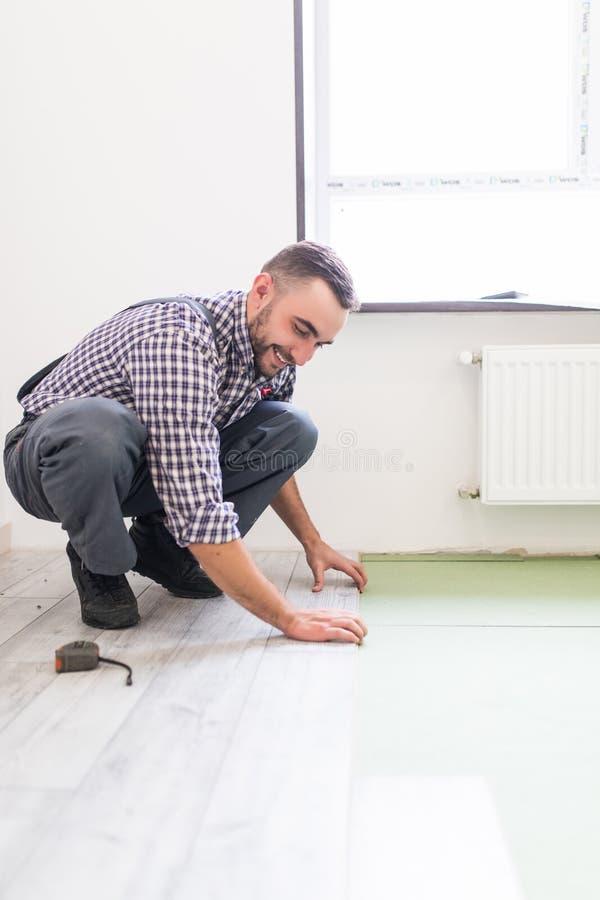Homem do trabalhador que coloca o revestimento estratificado no conceito da construção fotografia de stock royalty free
