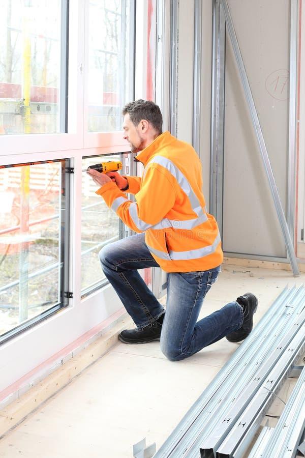 Homem do trabalhador que instala uma janela de madeira no canteiro de obras imagens de stock