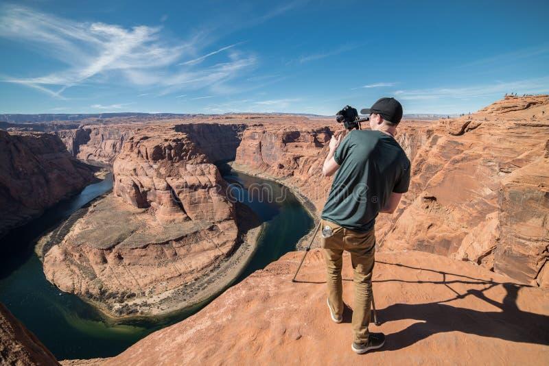 Homem do turista que toma a foto na câmera e o tripé durante seu curso em Grand Canyon, EUA fotografia de stock