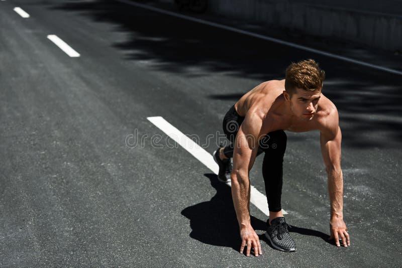 Homem do velocista no começo, pronto para ser executado fora Esportes Running fotografia de stock royalty free