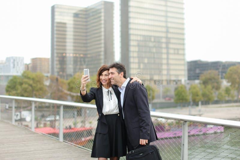 Homem do vendedor e de gerente da hora mulher que usa o smartphone que toma o sel fotos de stock