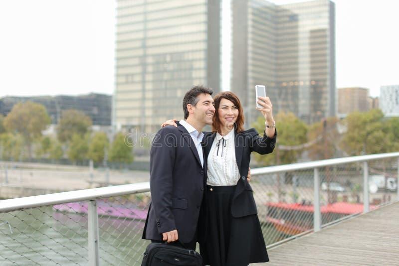 Homem do vendedor e de gerente da hora mulher que usa o smartphone que toma o sel fotografia de stock royalty free
