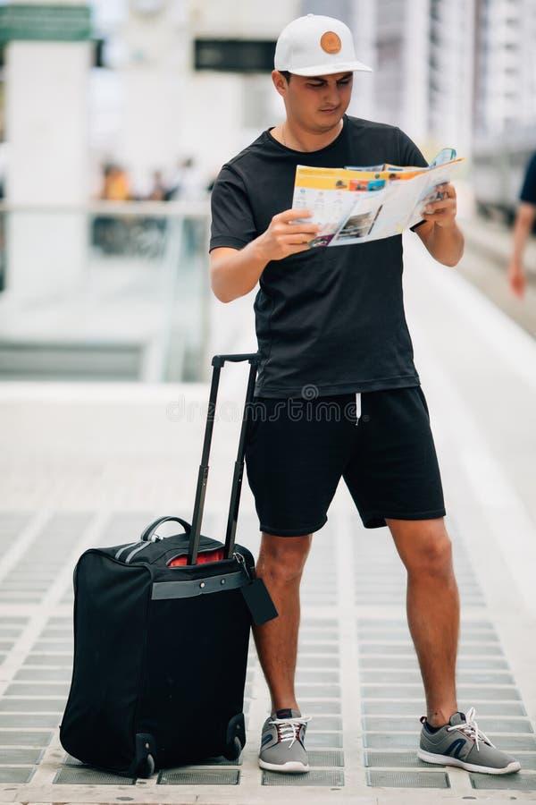 Homem do viajante com bagagem e mapa no estação de caminhos de ferro conceito do curso fotos de stock