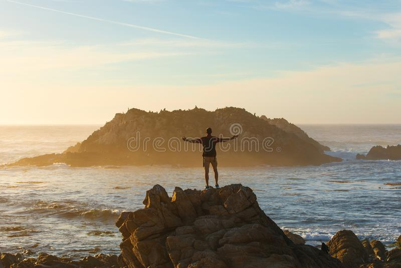 Homem do viajante com trouxa que aprecia a vista para o mar, caminhante do homem no por do sol, conceito do curso, Califórnia, EU fotografia de stock royalty free