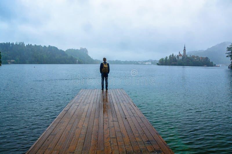Homem do viajante que está no cais de madeira do lago na névoa contra a ilha com igreja Conceito do estilo de vida do curso fotografia de stock