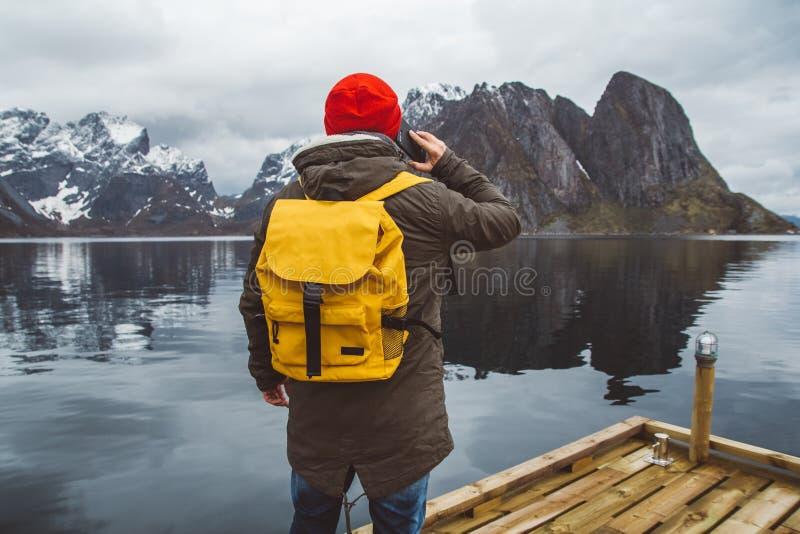 Homem do viajante do retrato que fala no telefone celular Turista em uma trouxa amarela que est? em um fundo de uma montanha e foto de stock