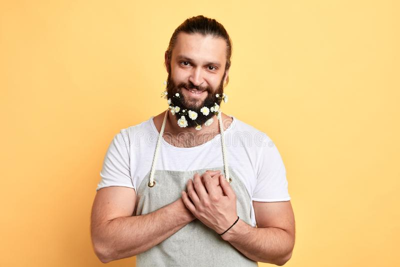 Homem doce emocional com uma barba decorada com as flores que mostram sua afeição imagens de stock royalty free