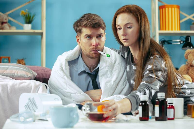 Homem doente com a febre que encontra-se na cama que manda a menina da temperatura tomar para ele foto de stock royalty free