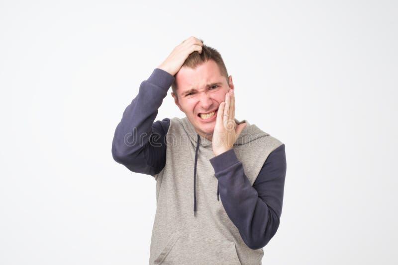 Homem doente deprimido que tem a dor de dente e mordente tocante foto de stock royalty free