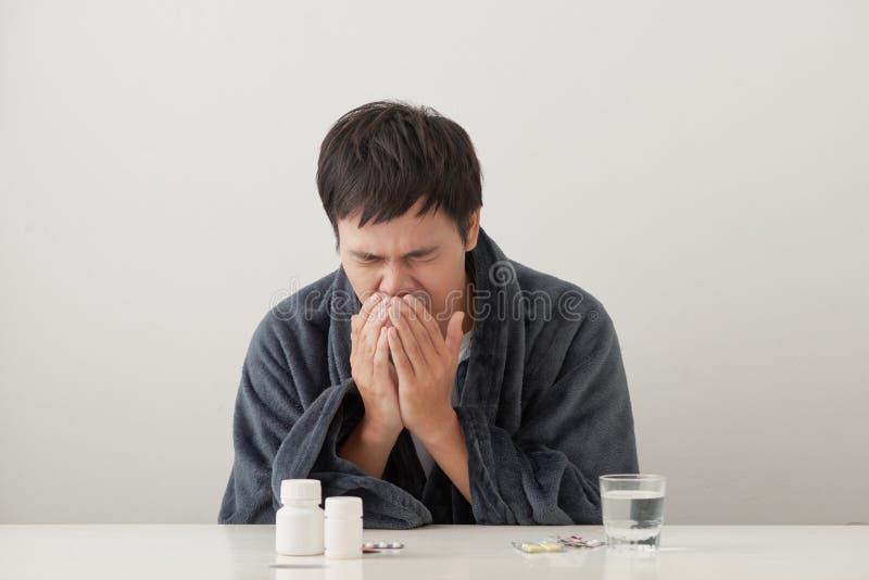 Homem doente e doente novo no tecido da terra arrendada do sof? que limpa o nariz descarado que tem a temperatura que sente mau c imagens de stock