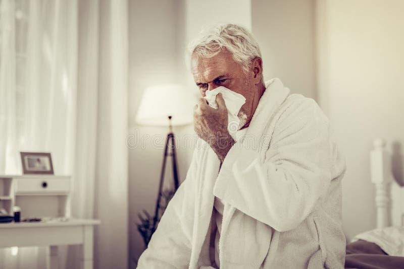 Homem doente idoso que funde seu nariz usando o tecido do papel imagem de stock royalty free