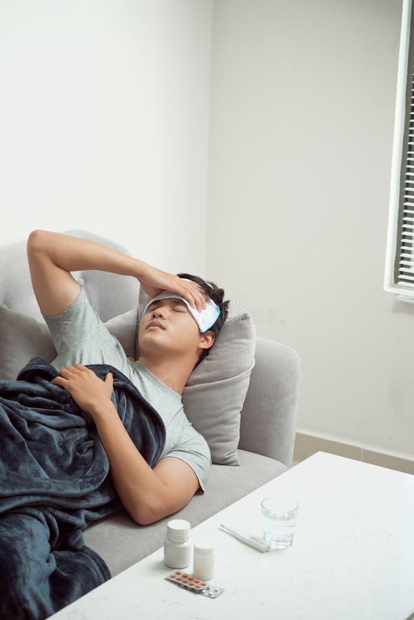 Homem doente que encontra-se no sof? que verifica sua temperatura sob uma cobertura em casa na sala de visitas fotografia de stock