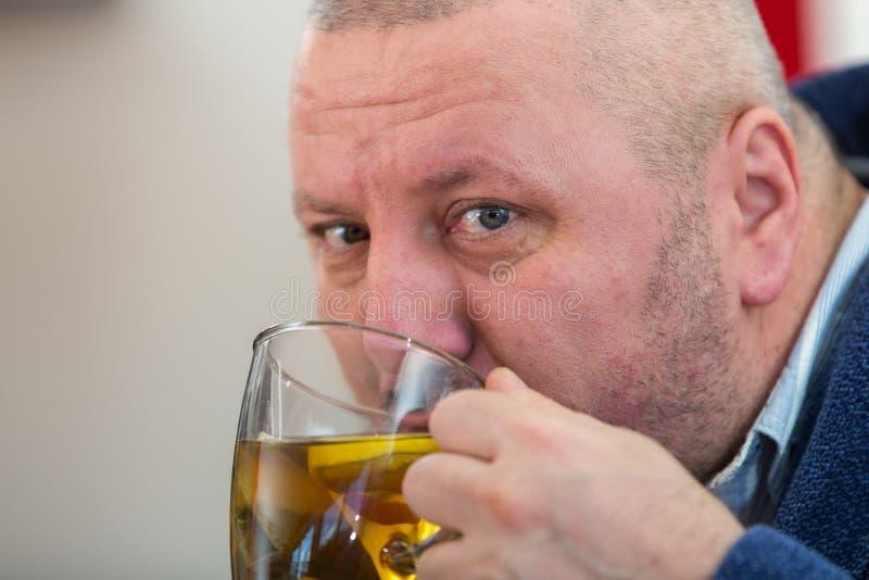 Homem doente que funde seu nariz com guardanapo de papel e que bebe o chá em casa foto de stock royalty free