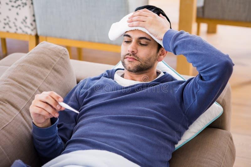 Homem doente que verifica sua temperatura imagem de stock
