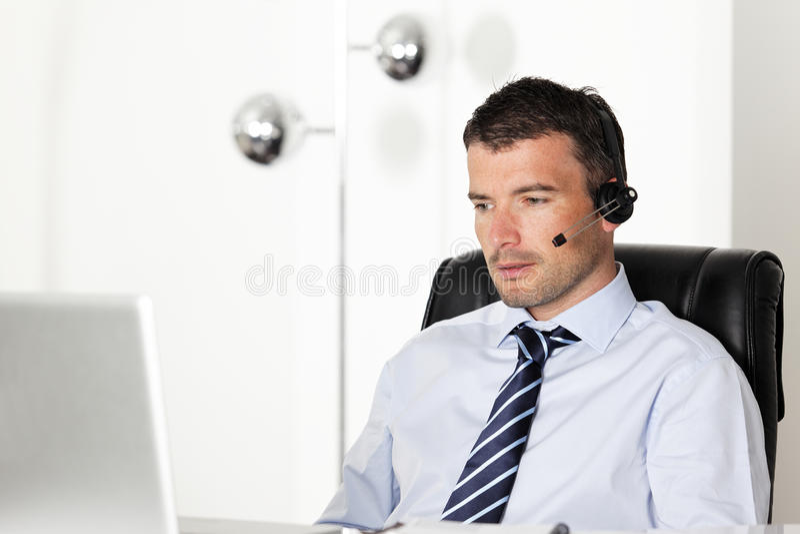 Homem dos auriculares do escritório fotos de stock royalty free
