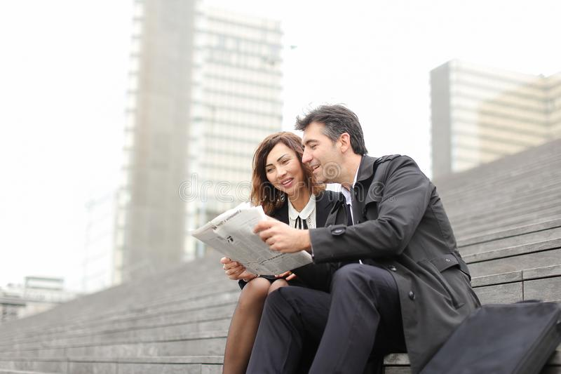 homem dos coordenadores e artigo fêmea da leitura sobre a empresa dentro fotografia de stock