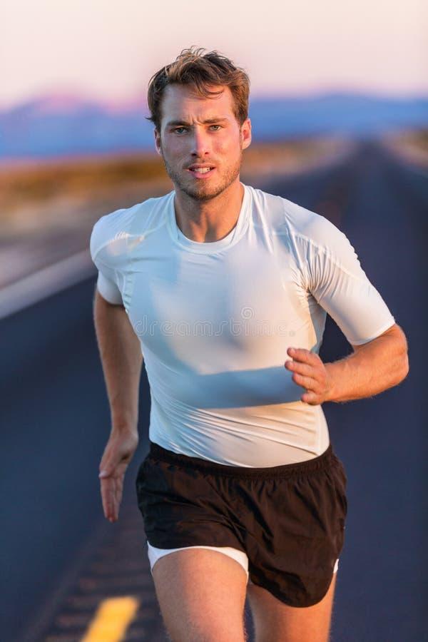 Homem dos esportes do corredor do atleta que corre na estrada do verão fotografia de stock royalty free