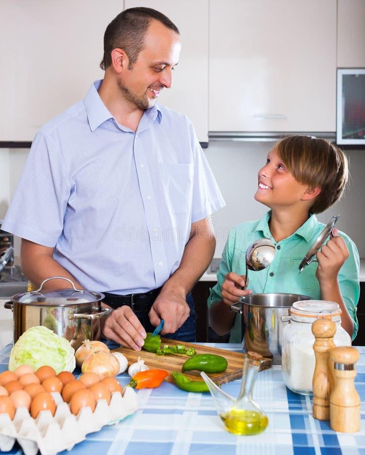 Homem e adolescente que cozinham junto fotografia de stock