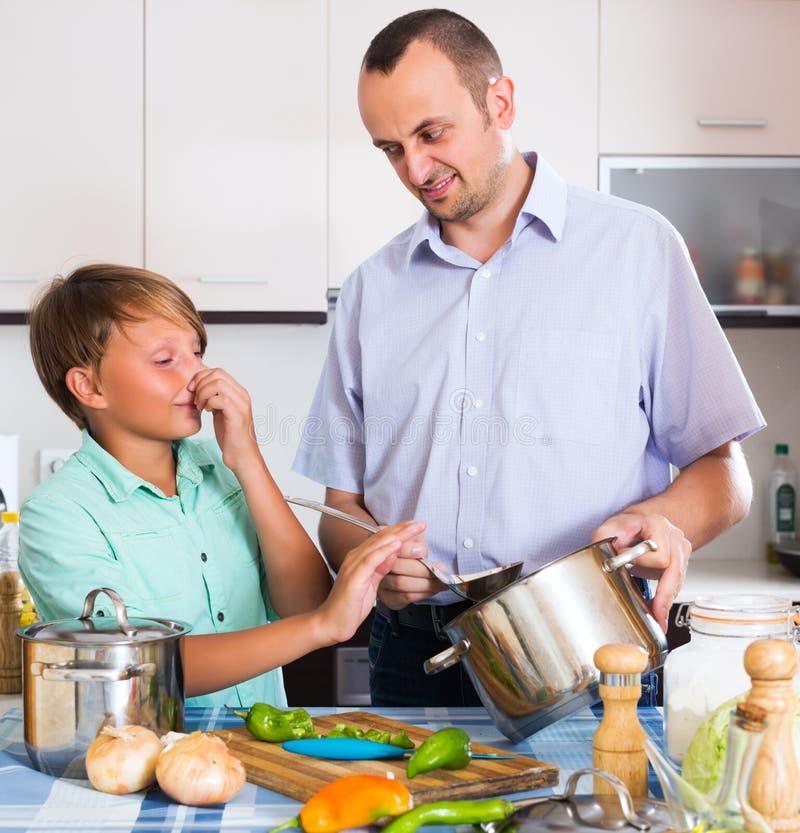 Homem e adolescente que cozinham junto imagens de stock royalty free